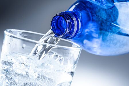 Photo pour Pouring mineral water from blue bottle into clear glass on abstract grey background. - image libre de droit