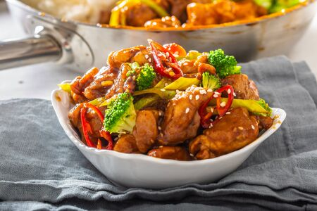 Photo pour Bowl of teriyaki chicken sprinkled with seesame seeds, fresh chillies and broccoli. - image libre de droit