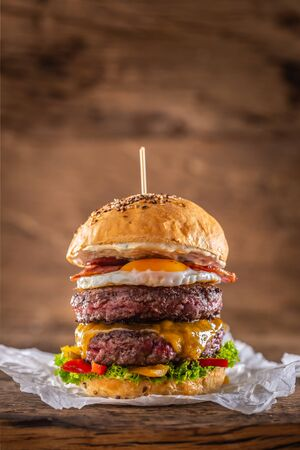 Foto de Double beef burger with cheese, fried egg, bacon, salad and peppers. - Imagen libre de derechos