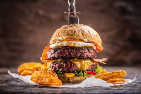 Photo pour A knife-stabbed double-beef burger with melted cheese, fried egg and bacon, salad and paprika potato wedges. - image libre de droit