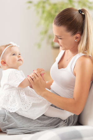 Photo pour Young mother plays with a baby girl on her lap. - image libre de droit