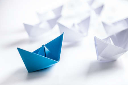 Photo pour Blue and white paper boats. Concept of leadership boats for teamwork group or success. - image libre de droit