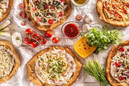 Photo pour Original hungarian langos with grated cheese and ketchup served o a table with other lovely and tasty doughs and vegetables. - image libre de droit