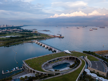 Photo for Aerial drone view of Singapore Marina Barrage with ships waiting out to sea - Royalty Free Image