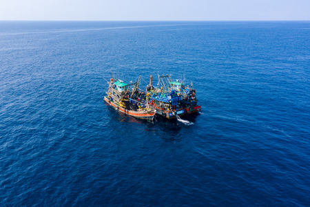 Foto de Overfishing - aerial view of a large fleet of fishing trawlers working together in a small area of the Andaman Sea - Imagen libre de derechos