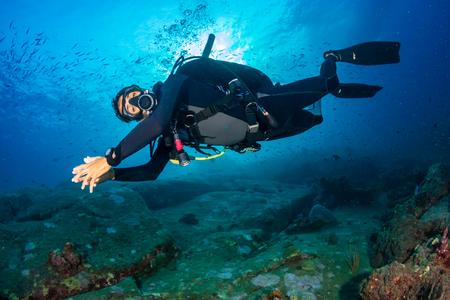 Photo pour SCUBA diver on a colorful, healthy tropical coral reef - image libre de droit