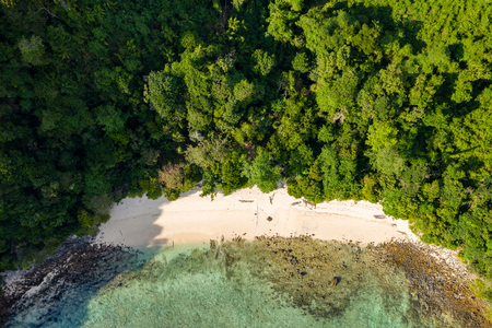 Aerial drone view of a small beach on a lush, green tropical island