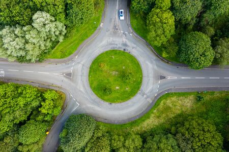 Photo pour Top down aerial drone view of a small traffic roundabout on a quiet road - image libre de droit
