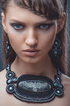 Photo pour Portrait of a beautiful woman with beautiful make-up and hairstyle. With the decoration of a large stone on a black background. - image libre de droit