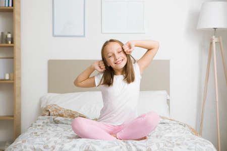 Photo pour Little girl in good mood in pajamas in the bedroom - image libre de droit