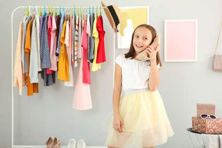 Photo pour Little cute girl chooses clothes in dressing room - image libre de droit