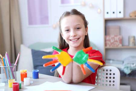 Photo pour Cute little girl draws paints at home. - image libre de droit