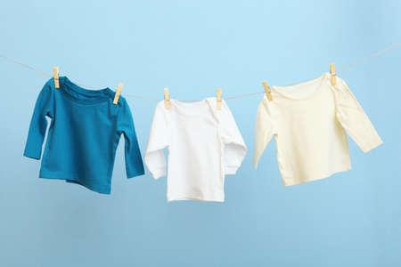 Photo pour Baby clothes on a rope on a colored background. - image libre de droit