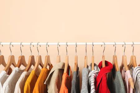Photo pour fashionable clothes on hangers on a wardrobe rack on a colored background. - image libre de droit