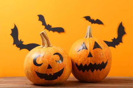 Foto de pumpkins with painted faces on a colored background for Halloween. - Imagen libre de derechos
