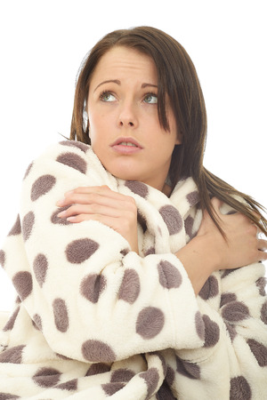 Frightened Scared Attractive Young Woman Against A White Background Wearing A Warm Cosy Dressing Gown