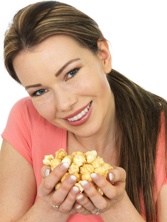 Attractive Young Happy Smiling Woman Holding A Handful Of Toffee Coated Popcorn