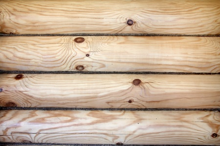 A piece of a wall in a house made of logs. Wood texture
