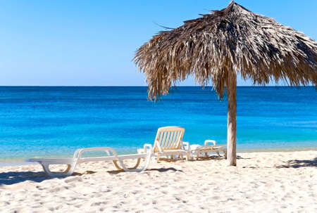 The idyllic beach with deck chairs and umbrella, Ancon, Cuba