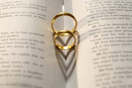 Photo pour Two wedding Ring on the bible with shadow of heart shape on the page - image libre de droit