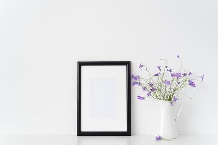 Foto de Black portrait frame mockup with wild flowers in vase near white wall. Empty frame mock up for presentation design. Template framing for modern art. - Imagen libre de derechos