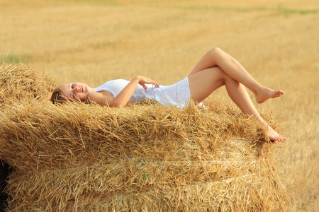 Young attractive barefoot girl lying on a bale of yellow straw at fieldの写真素材
