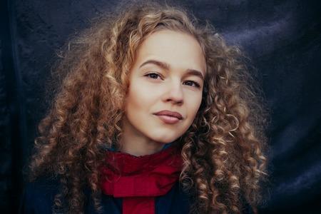Photo pour Close-up portrait of beautiful model with long curly blond hair on black background - image libre de droit
