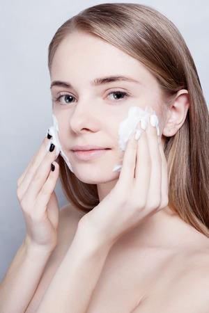 Photo pour Close-up woman clears skin foam on a gray background - image libre de droit
