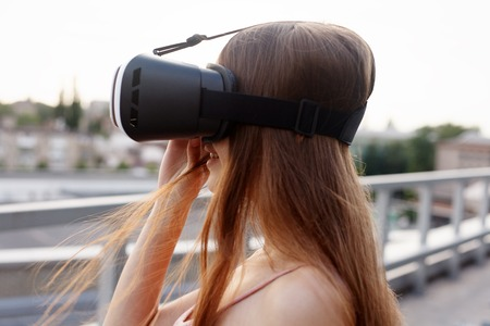 business,technologies, VR, people and lifestyle concept - amazed young beautiful girl using new VR technology VR gear on market amazing sights on oculus headset 3D video glasses VR headset 360 video