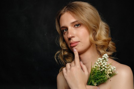 Photo for beautiful young transgender with blond hair, dark blue background, smiling, holding flowers and white cloth - Royalty Free Image