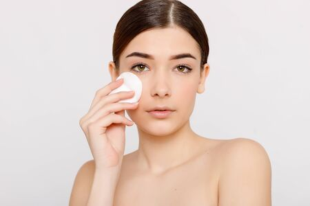 Photo pour Healthy fresh girl removing makeup from her face with cotton pad. Beauty woman cleaning her face with cotton swab pad isolated on grey background. Skin care and beauty concept. - image libre de droit