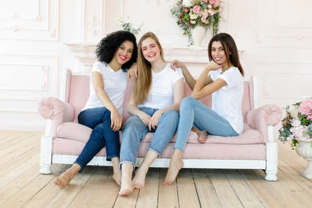 Photo pour friendship and happiness concept - three girlfriends having a talk at home. Three happy funny multi ethnic ladies best friends laughing having fun, pretty diverse women wear white t-shirts and jeans - image libre de droit