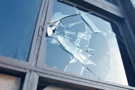 smashed window reflecting blue sky