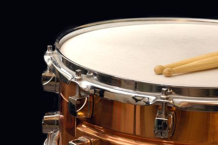 copper snare drum and sticks on black