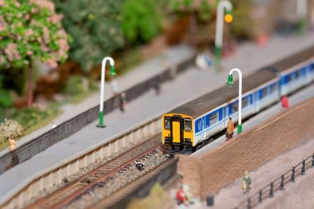 miniature model commuter train in a station with shallow d.o.f