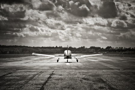 sepia toned propeller aircraft taking off into turbulent looking clouds
