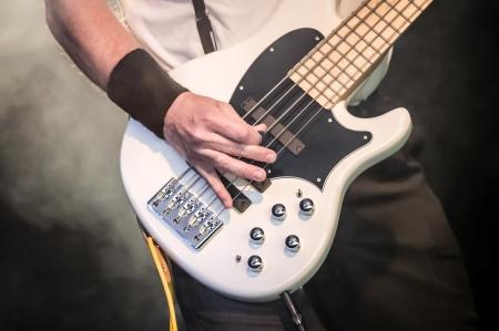 hand of a musician playing a five string bass guitar