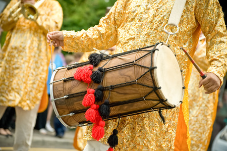 musician playing a traditional asian dhol drum