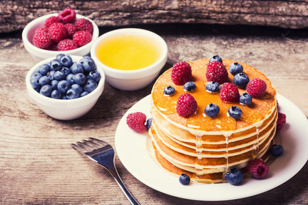 Pancakes with blueberries, honey & raspberry on wood background