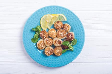 Photo pour Fried scallops with lemon and salad . Seafood background - image libre de droit