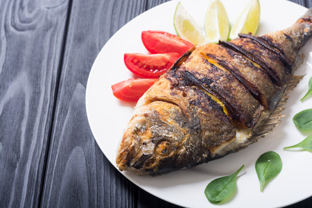 Photo pour Fried fish dorado with lime , tomatoes and spinach . Sea food background - image libre de droit