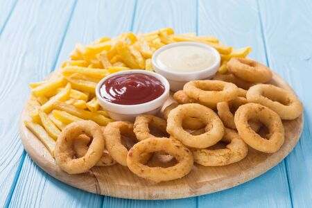 Photo pour French fries and onion rings with sauces on wooden board - image libre de droit