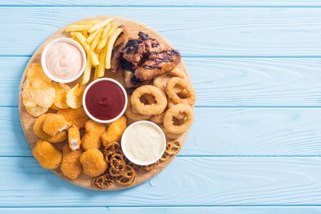 Foto de Onion rings , nuggets grilled wings , french fries mix of snacks and sauces . Beer board - Imagen libre de derechos