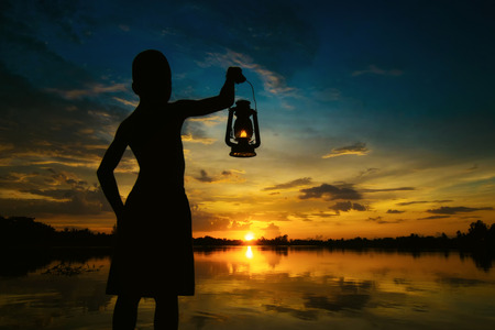 boy holding Lamp looking for sunset . Abstract meaning hope of life.