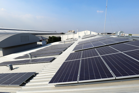 Photo for Solar PV on Industrial Roof with Exhaust Duct Chimneys - Royalty Free Image