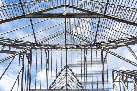Roof frame of business building under construction against blue sky.