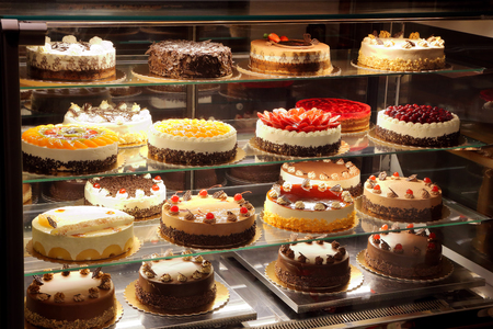 Photo pour Different types of cakes in pastry shop glass display - image libre de droit