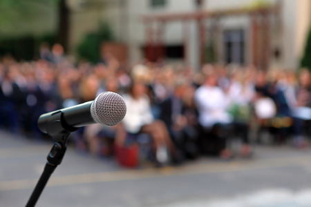 Foto de Microphone and stand in front of graduation ceremony audience against a background of auditorium and empty space for text - Imagen libre de derechos