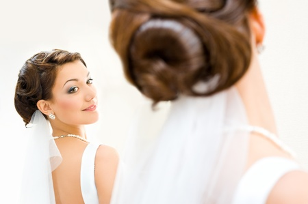 Photo pour young bride looks at herself in the mirror - image libre de droit