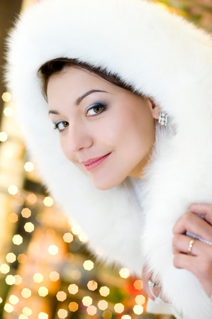 young brunette woman in white fur hood against sparkling background